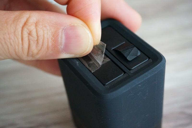 デュアルバッテリーチャージャーのバッテリーをセロハンつまみで引き抜くところ