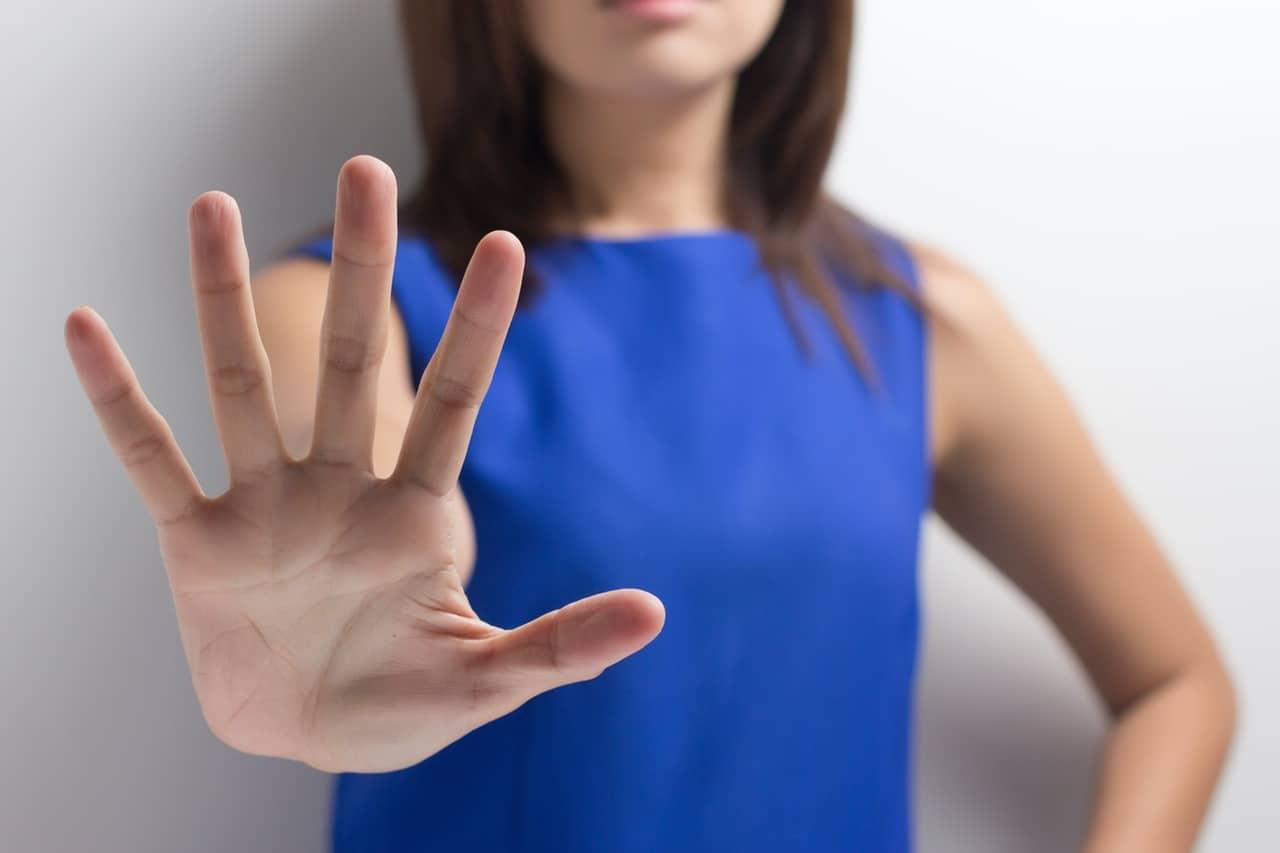 手を出して拒否する女性